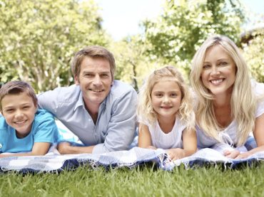 Portrait of a happy family sitting on a picnic blanket in a park